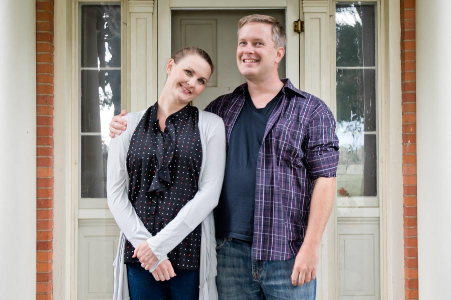 Couple standing in front of home asking what a wealth advisor is