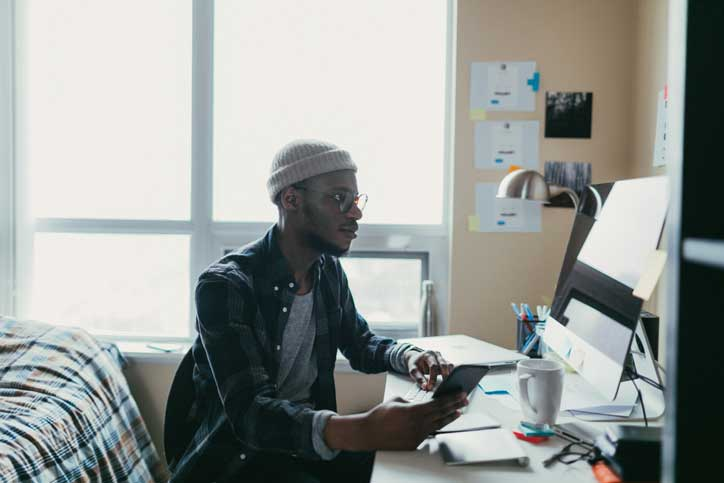 Student working on computer in dorm room