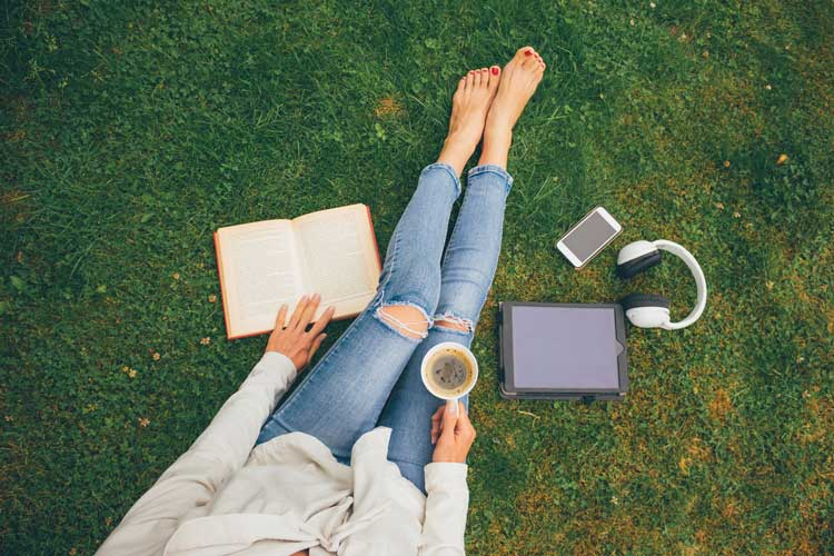 woman sitting on grass with book and coffee